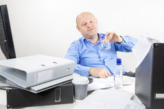 Drunk businessman drinks alcohol at the office Royalty Free Stock Image