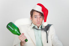 Drunk businessman has dressed Christmas cap Stock Image