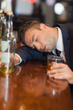 Drunk businessman holding whiskey glass lying on a counter Stock Images