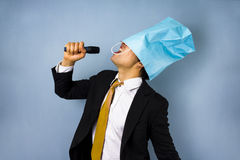 Drunk businessman singing karaoke. With a pape rbag over his head Royalty Free Stock Photography