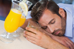 Drunk businessman sleeping on bar beside cocktail Royalty Free Stock Images