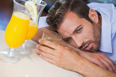Drunk businessman slumped on bar beside cocktail Royalty Free Stock Image