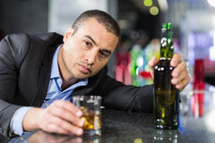 Drunk businessman slumped on bar Stock Images