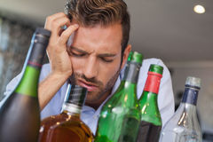 Drunk businessman slumped beside many spirit bottles Royalty Free Stock Image