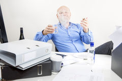 Drunk businessman smokes and drink at office Royalty Free Stock Photos