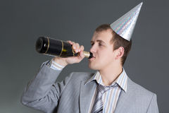 Drunk businessman with bottle of champagne over grey Royalty Free Stock Photos
