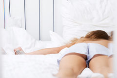 Drunk caucasian woman lying in bed Royalty Free Stock Image