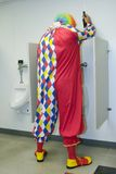 Drunk Clown in Urinal. Picture of adult clown with beer bottle in men's urinal Royalty Free Stock Photography