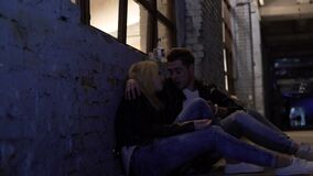 Drunk couple sitting on floor near wall and talking, nightlife, hook-up. Stock footage stock video