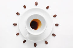 Drunk cup of coffee and coffee beans against white background forming clock dial viewed from top Royalty Free Stock Photos