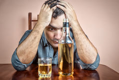 Drunk and depressed hispanic  man suffering a headache. (with a liquor bottle on a table Royalty Free Stock Images