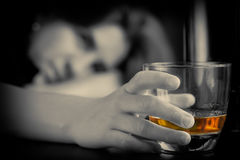 Drunk and depressed lonely woman. Holding a glass of whisky with a sad expression Royalty Free Stock Photos