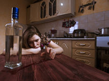 Drunk depressive woman looks at the bottle with alcohol Stock Image