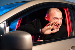 Drunk driver on the background of police car light. Male drunk driver sitting in his car on the background of police car lighting Royalty Free Stock Photo