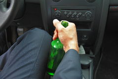 Drunk driver with bottle. In his hand Royalty Free Stock Image