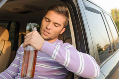 Drunk driver with a bottle of wine Stock Photo