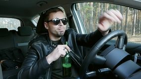 Drunk driver drinking beer while driving, traffic offense. Drunk driver drinking beer while driving in slow motion, traffic offense stock footage