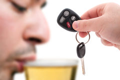Drunk Driving. Concept with a hand holding some car keys and a man drinking beer in the background.  Shallow depth of field Royalty Free Stock Image