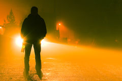 Drunk Driving Accident. A silhouette of a drunk person standing on the road on a foggy night holding a bottle Stock Images