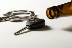 Drunk Driving. A beer bottle on its side with handcuff and car key Stock Photography