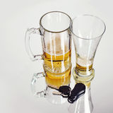 Drunk Driving Beer Glasses with Keys on White. Two empty glass beer glasses with car keys on a white background for a dwi or drunk driving concept Royalty Free Stock Images