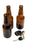 Drunk Driving Concept. Some car keys shot alongside some empty beer bottles, isolated against a white background Royalty Free Stock Photo