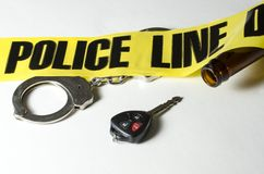 Drunk Driving. Crime scene tape across handcuffs and a beer bottle Royalty Free Stock Photo