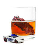 Drunk driving. DUI concept. Image of a drunk driving accident inside a small glass with beer isolated on a white background Royalty Free Stock Photos