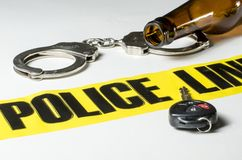 Drunk Driving. Police tape with a beer bottle, handcuffs and car key Stock Image