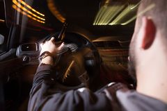 Drunk Driving, Speeding, Being too Tired to Drive are Potential Concepts for This Image of Blurry Road at Night. Man drink beer while driving car. Driving in a stock photography