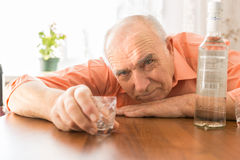 Drunk Elderly Holding Shot Glass at the Table. Close up Drunk Elderly Holding Small Shot Glass at the Wooden Table with Vodka While Looking at the Camera Stock Photos