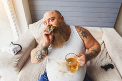 Drunk fat man eating unhealthy food Stock Images