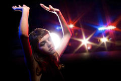 Drunk Female Bring Arrested. Young drug intoxicated female holding her hands up while being arrested Stock Image