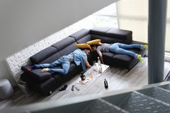 Drunk Friends Sleeping On Sofa In Messy Room After Party royalty free stock images