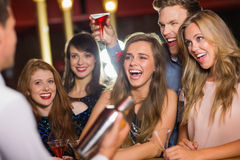 Drunk friends watching barman making cocktail Royalty Free Stock Photo