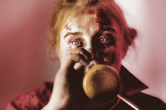 Drunk ghoul sculling beer at Halloween party. Creepy portrait of a drunken female ghoul drinking beer at Halloween party event Royalty Free Stock Photos