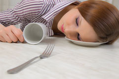 Drunk girl. A girl who is sleeping, lying down in the face of the plate Stock Photography