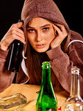 Drunk girl holding green glass bottle of vodka. Royalty Free Stock Image