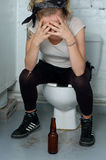 Drunk girl in a public toilet. Simulation with real punk girl Stock Photos