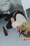 Drunk girl in a public toilet 4 (focus on head, left hand & bottle) Stock Image