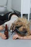Drunk girl in a public toilet (focus on head, hands & bottle) Stock Photos