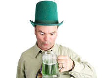 Drunk With Green Beer on St Patricks Day. Drunk Irish-American man looks into his green beer on St. Patrick's Day.  Isolated on white Stock Image