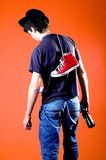 Drunk Guy. Young man or teenager, walking with beer bottle in one hand, red hightop shoes slung over shoulder, hat on crooked, orange background stock photo