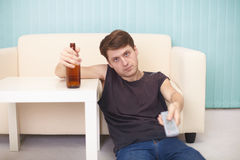Drunk guy with bottle of beer, TV changes channels Royalty Free Stock Images