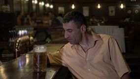 Drunk guy drinking beer alone at the bar in a pub and falling asleep on the bar -. Drunk guy drinking beer alone at the bar in a pub and falling asleep on the stock video