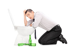 Drunk guy leaning over a toilet Royalty Free Stock Photos