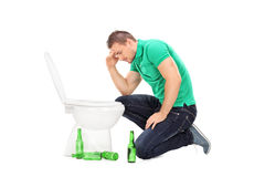 Drunk guy leaning over a toilet Royalty Free Stock Images