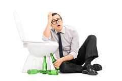 Drunk guy leaning on a toilet seat Royalty Free Stock Photography