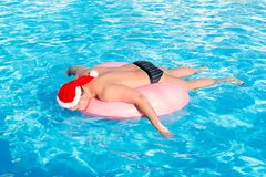 A drunk guy in santa claus hat swims on inflatable circle in the pool. travel of a Russian tourist.  royalty free stock photography