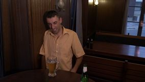 Drunk guy sitting a table in a pub cannot hold his glass with beer -. Drunk guy sitting a table in a pub cannot hold his glass with beer stock video footage